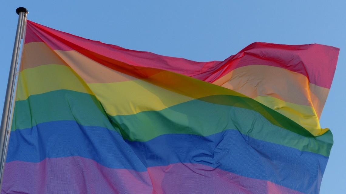 A rainbow flag against a blue sky