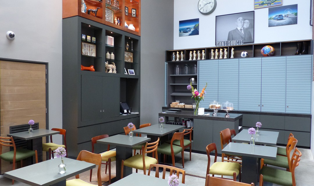 A corner space with modern, grey tables and cupboards along the walls