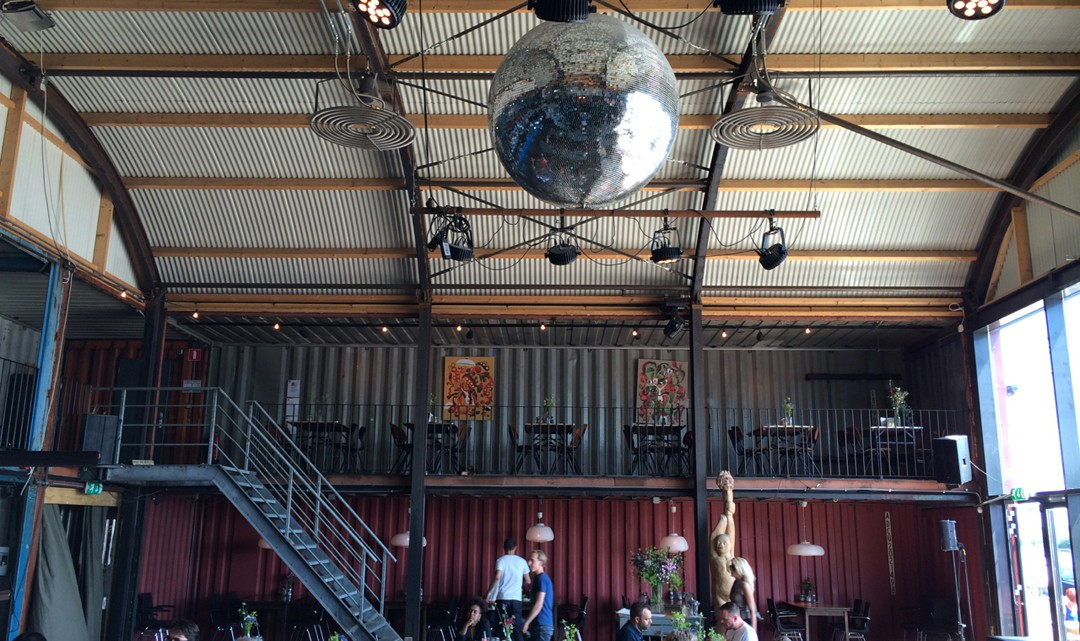 A big mirror ball on the curved , corrugated ceiling and in the background the stairs to the balcony
