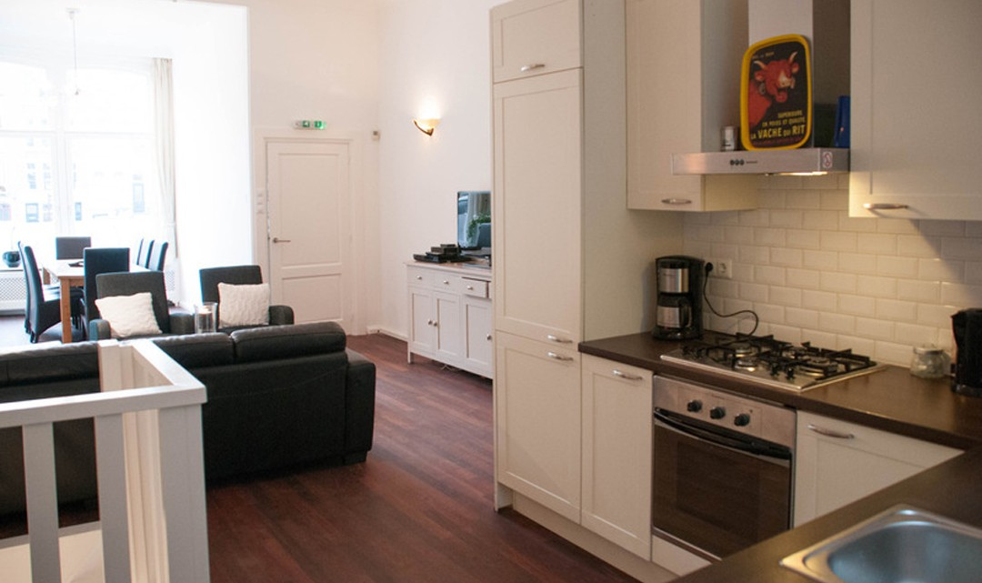 Part view of the white, modern kitchen and the leather couches in the living area