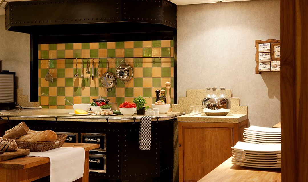 The kitchen with a copy of a historic looking stove, with white and green blocked tiles as splashback