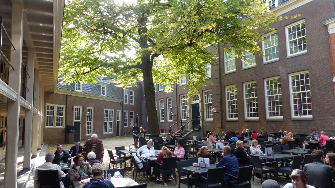 A busy terrace in the shade of a large tree on a sunny day