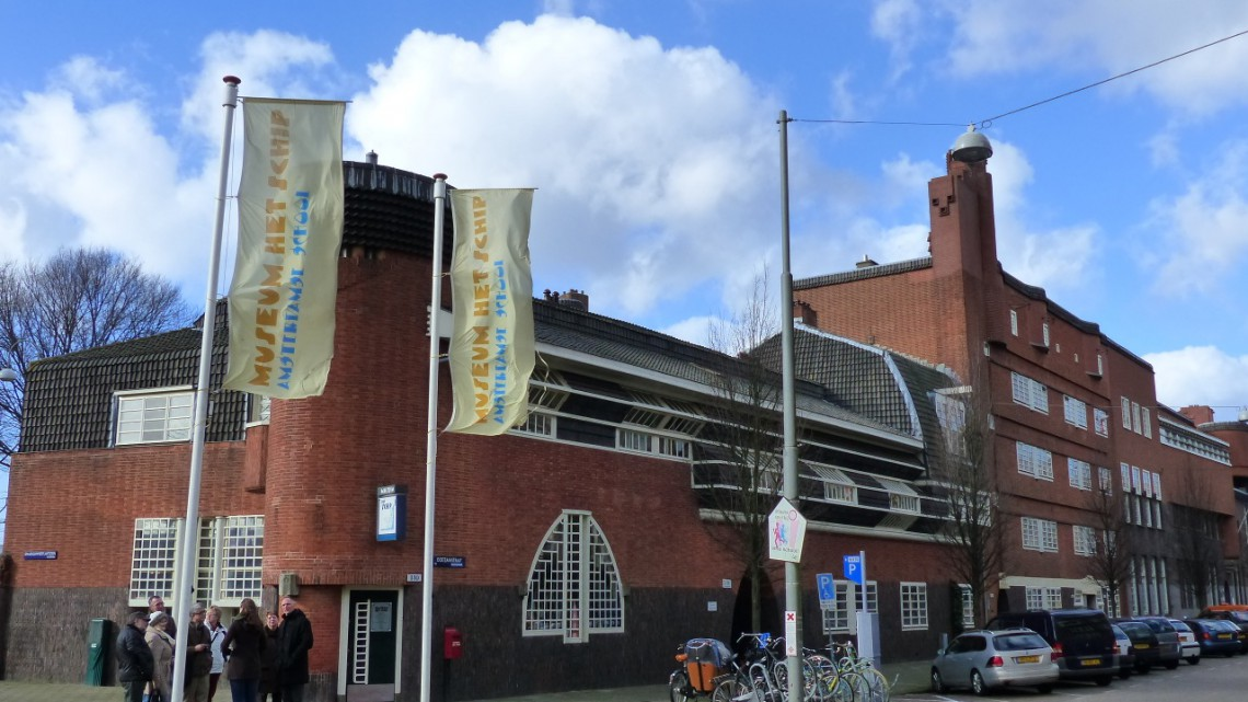 Peoppe standing in front of the entrance of the museum with promotional flags on the foreground