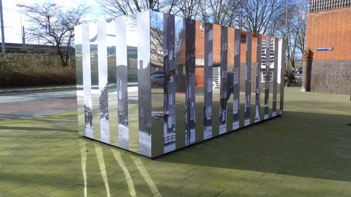 A mirrored, striped box-like container on the square in front of the museum