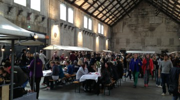 Food stands and long table with snacking people in an enormous industrial looking hall