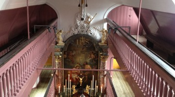 A view from the second balcony, with pink balustrade, into the small, narrow church towards the altar