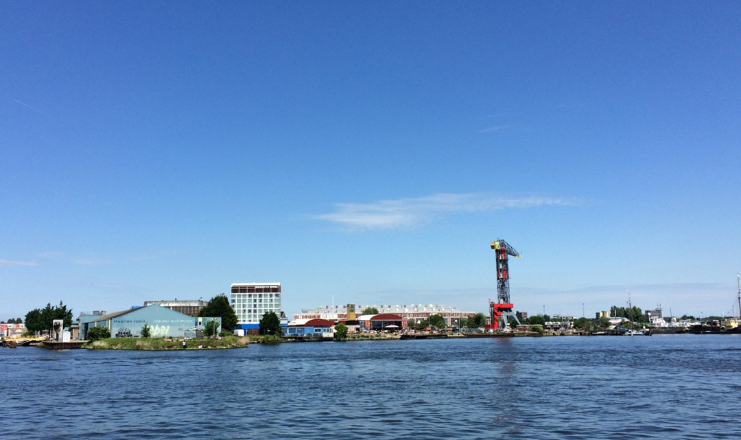 A view from the river IJ, with Pllek in the middle of the other buildings on NDSM Werf