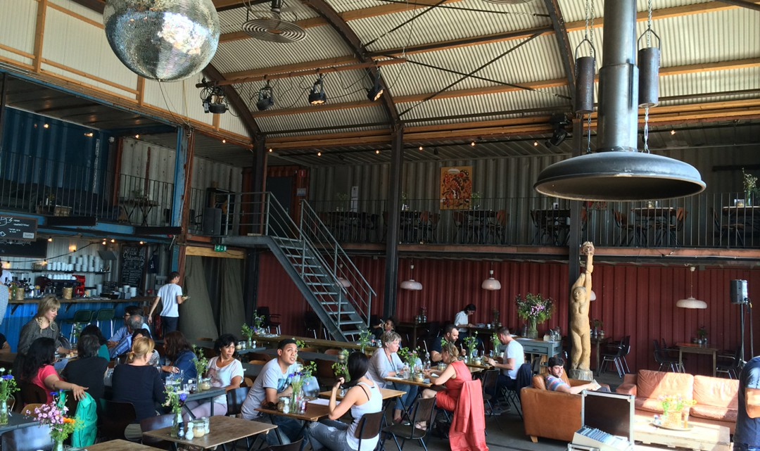 A view over the restaurant area inside with in the background the stairs to the balcony seating area