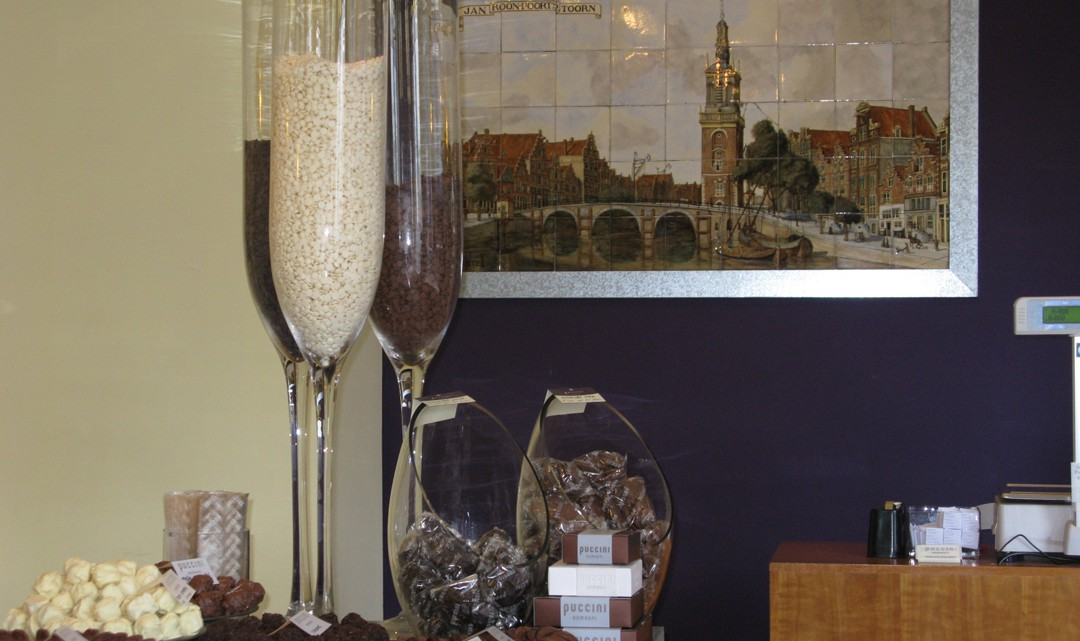 Big chapagne-like glasses with white and brown chocolate buttons. On the wall behind them a tiled of the bridge in front of the shop that once had tower