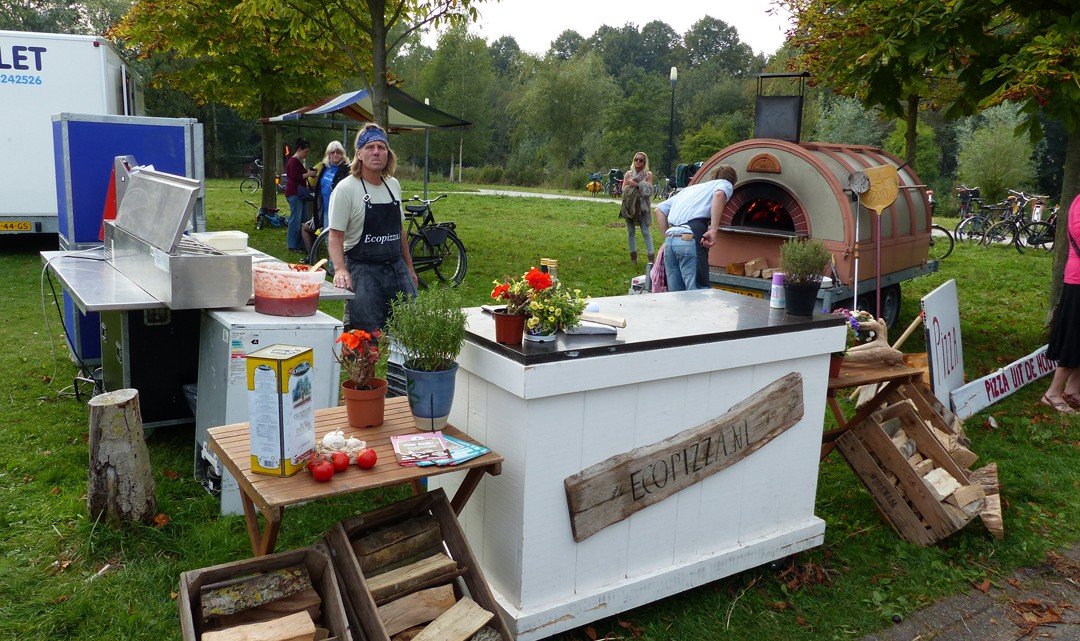 A basic counter on the grass. Behind it a mobile wood-fuelled pizza oven