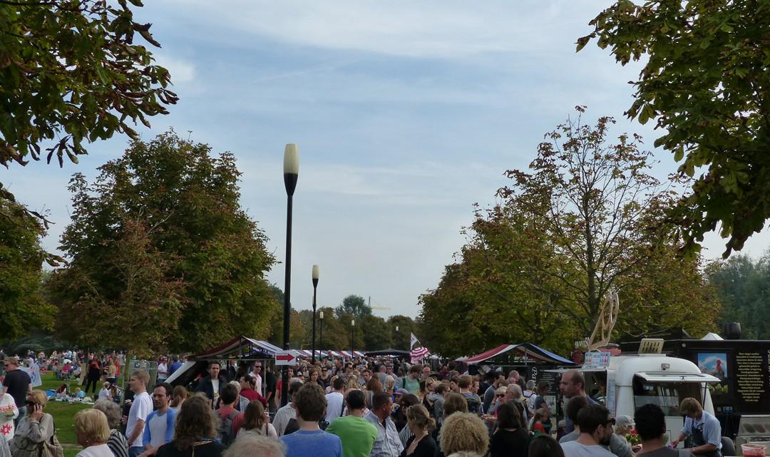 Many people strowling alongside the market stalls