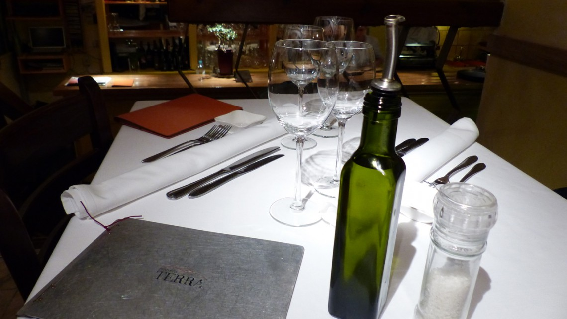 A set table with glasses, olive oil and the menu