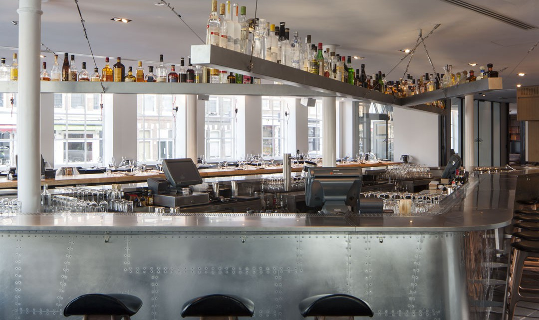 A closer look of the metal coated bar with bottles of liquor above the bar