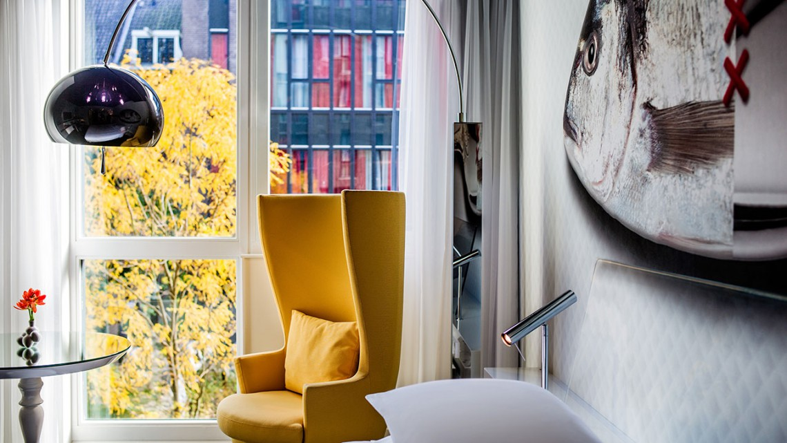 A yellow chair in front of the hotel room's window