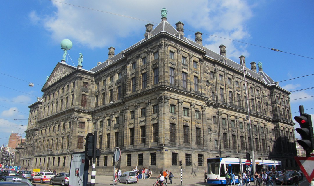 The palace is a squared building of semi-dark, dirty stones. In the front is a tram and people in traffic