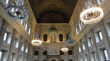 A view towards the chandeliers, the impressive statue of Atlas and the richly decorated windows and support columns