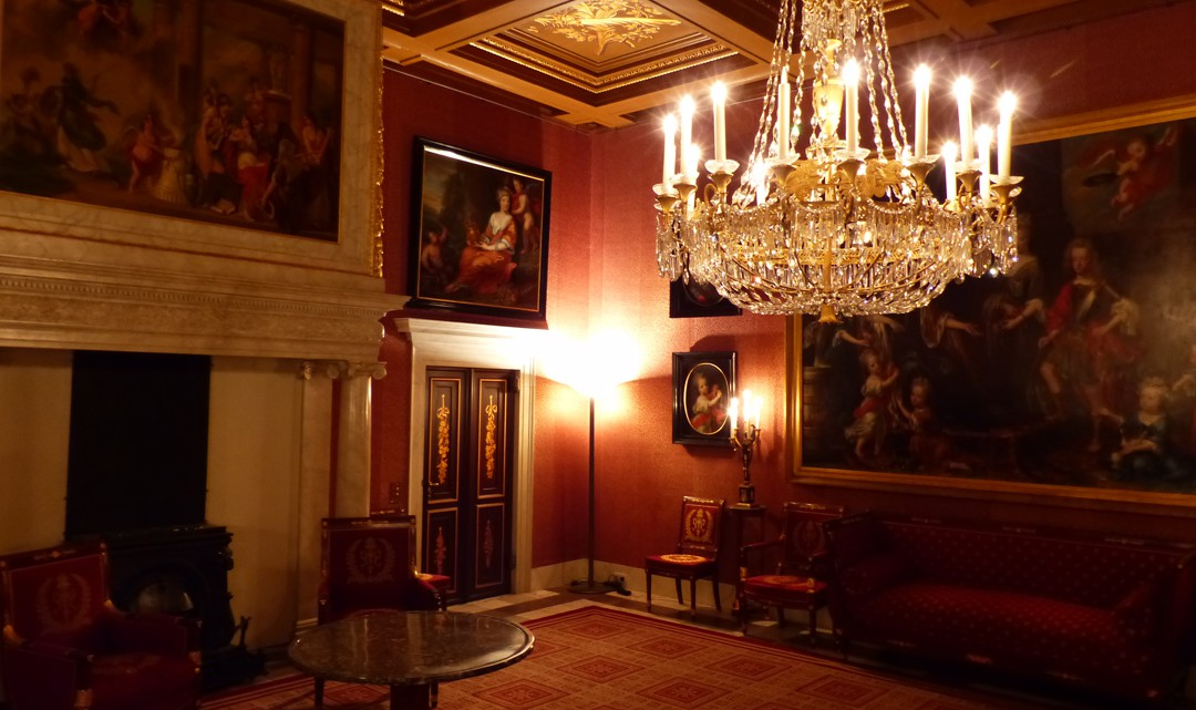 A richly decorated red-brown room with one chandelier and walls full of paintings