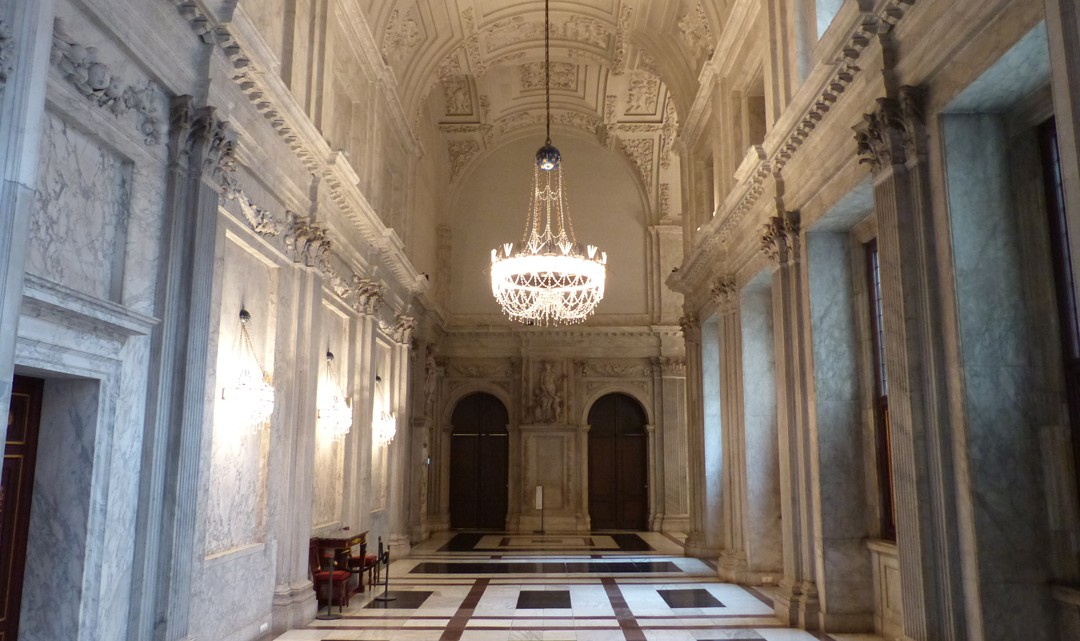 A light and high corridor with richly plastering on the ceiling and marble walls