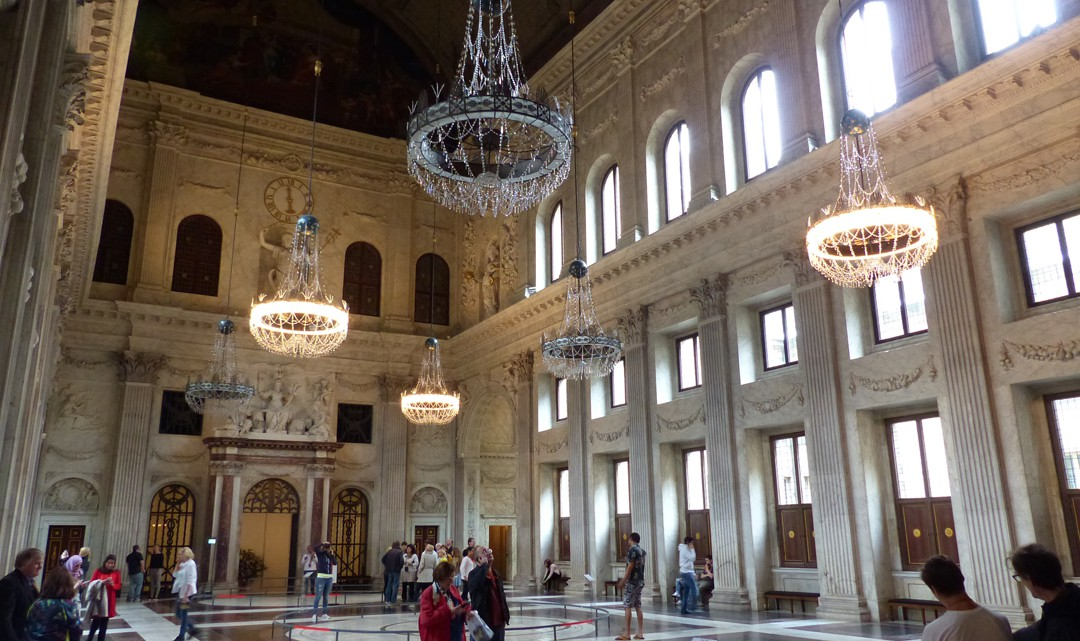 An enormous hall with wooden vault ceiling, marble walls and floor and six enormous chandeliers that look quite small