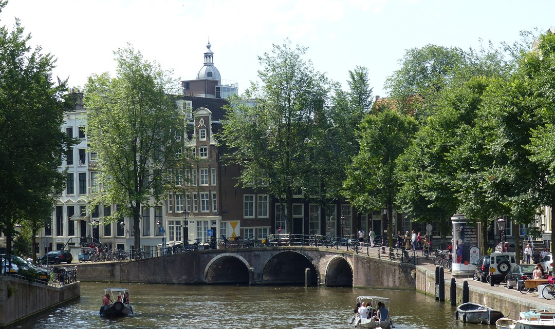 View over the Herengracht canal with two electric boats passing each other in opposite direction