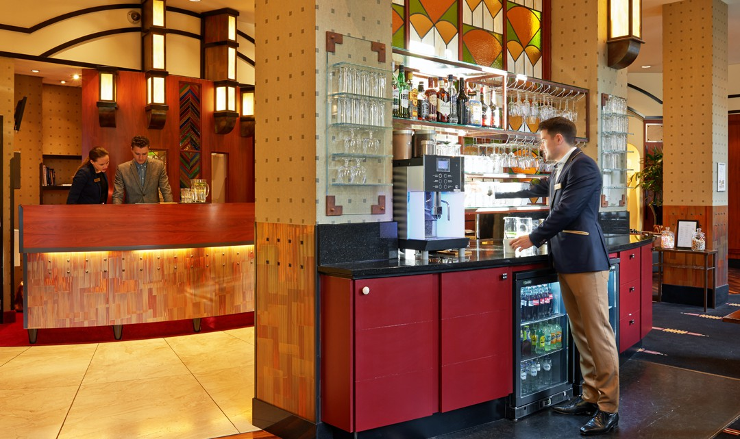 A self-service bar/wall with glasses and liquor, a coffee machine and a fridge