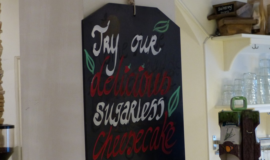 A blackboard sign with the text: Try our delicious cheesecake