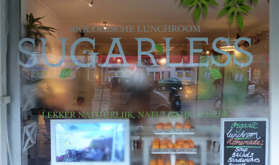 The front window with the name of Sugarless , some organic fruit and a sign mentioning they are an organic lunchroom with homemade food