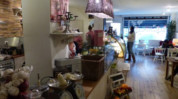 A view of the interior towards the front door. On and in front of the counter there are many organic vegetables and other ingredients displayed