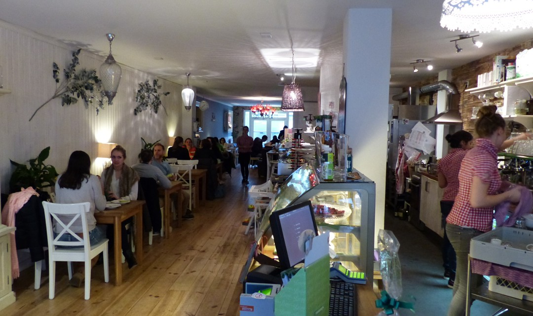A view towards the back with occupied tables and chairs on th left and the counter/kitchen on the right