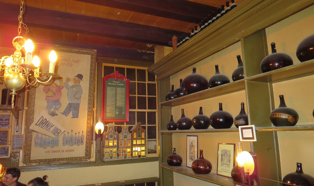 Shelves with dusty distillery bottels on the right side and an old promotion poster in the back of the room