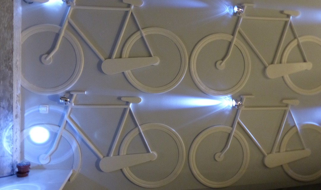 Plaster against the wall in the shape of bikes with working front bike lamps