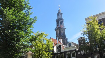 The church tower peeping out above Amsterdam canal houses