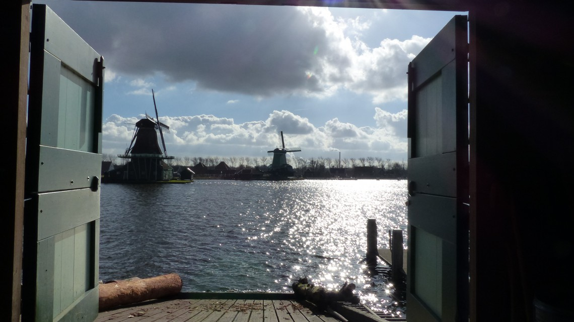 A view from open doors to two windmills along the water with Dutch clouds and sun