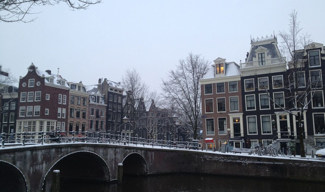 Snow on bridge and Amsterdam canal houses